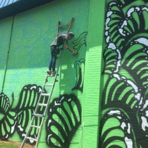 Jess Ulrich painting the ReStore mural