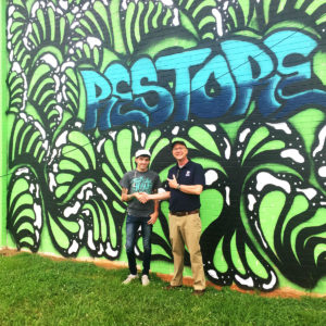 Artist standing in front of the mural with Habitat rep
