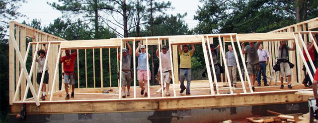 Madison County Habitat volunteers raise a wall on a new home