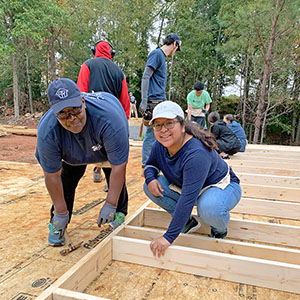 Future homeowner Fay Hill and volunteers on the Kinda Tiny Homes build site