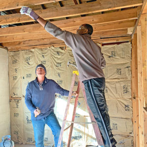 A Zaxby's employee helps renovate a house in Athens, GA