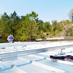 A worker installs aluminum rails on a metal roof to prepare for a solar panel installation